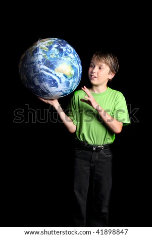 A young boy student looks at the world with amazement and curiosity against a dark background. Slight motion in left hand - stock photo