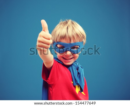 A young boy superhero giving you a thumbs up - stock photo