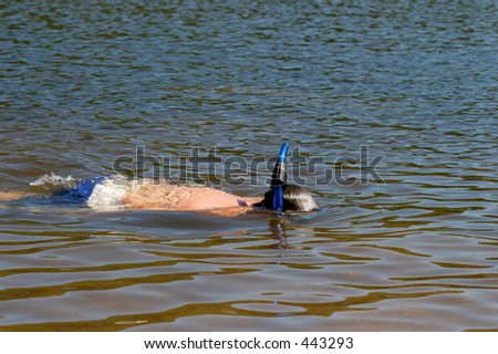 a young boy swimming and cooling off on a hot summer day - stock photo