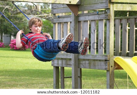 A young boy swinging on an outdoor swing. - stock photo