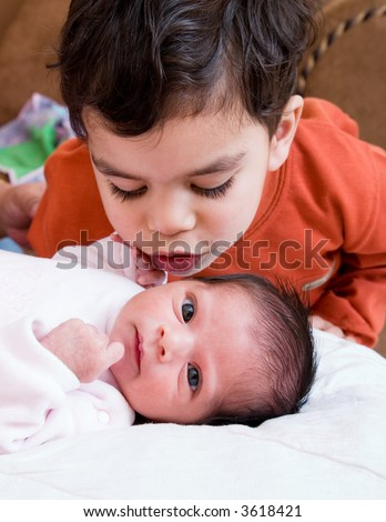 A young boy talking to his newborn sister - stock photo