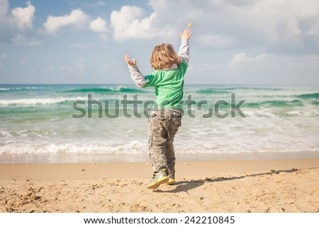 A young boy throws rocks into an ocean.   - stock photo