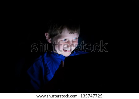 a young boy using an electronic tablet device. Light coming from the tablet - stock photo
