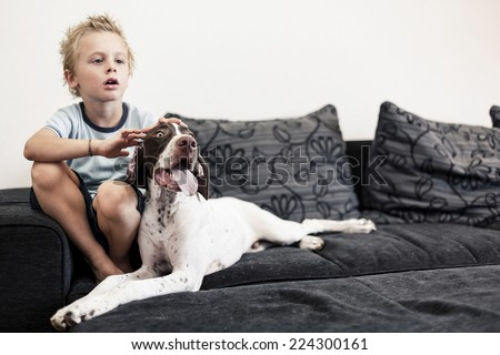 A young boy watching TV on the sofa with his big puppy. - stock photo