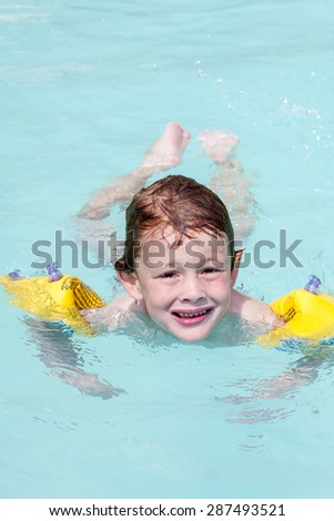 A young boy wearing armbands swimming in a swimming pool - stock photo