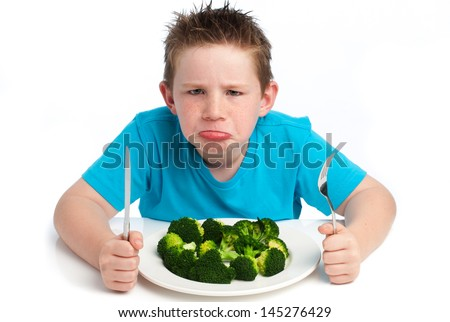 A young boy who is not happy about eating his broccoli. Isolated on white background. - stock photo