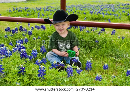 A young boy with a cowboy hat sits near a fence - stock photo