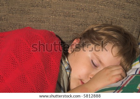 A young boy, with a dirty face, sleeping - stock photo