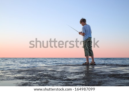 A young boy with a fishing rod fishing in the sea - stock photo