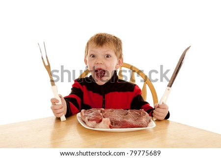 A young boy with a happy expression on his face with a large steak on his plate holding a big knife and big fork.