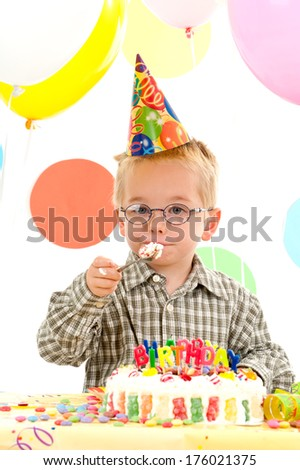 A young boy with a party hat eats a cake.