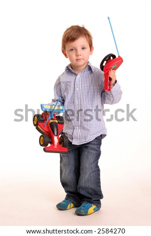 A young boy with a remote controlled car isolated on a white background - stock photo