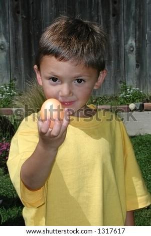 A young boy with big brown eyes shows off the easter egg he found.