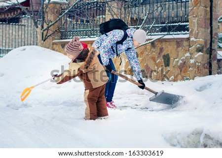 A young boy with his aunt clearing the yard - stock photo