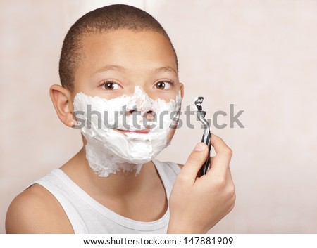 A young boy with no beard experiments with his father's shaving utensils. - stock photo
