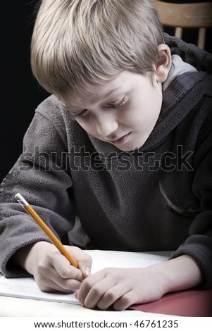 a young boy works on his homework with a pencil
