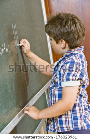 A young boy writes on chalkboard with chalk.