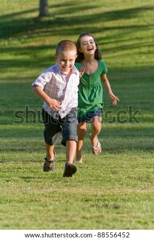 A young brother and sister running through a green grassy field with smiles on their faces. - stock photo