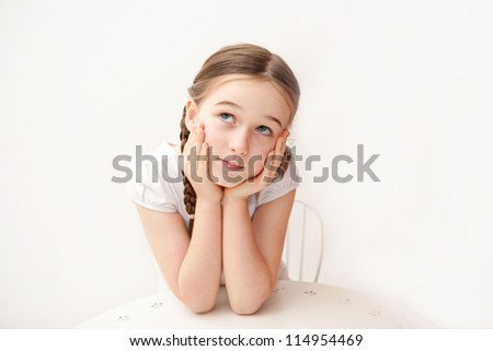 A young brunette girl against a white background is thinking and looks confused or inquisitive