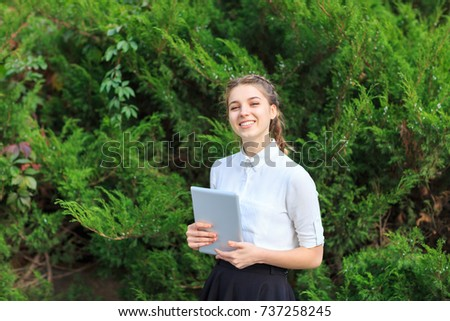 A young brunette girl sits in a park with a tablet.