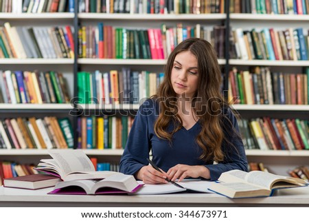 A young brunette girl who is sitting at a desk in the library with an open note book writing out information from many opened books around her, looking at a book, a concept of studying and research - stock photo