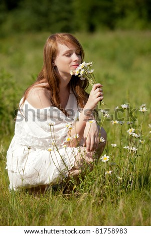 A young brunette lady picks flowers on a summer meadow