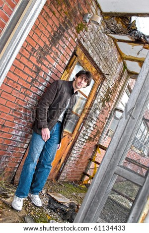 A young brunette man posing outside a worn and abandoned building. - stock photo