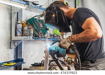 A young brunette man welder in a black T-shirt, in a welding mask and  welder leathers, welds a metal welding machine in the workshop, sparks fly in the sides