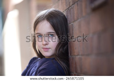 A young brunette teen girl in a alley looking contemplative and alone