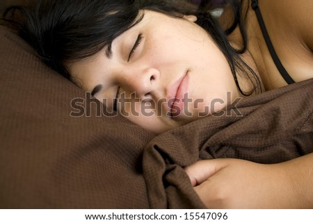 A young brunette woman is fast asleep in her bed.