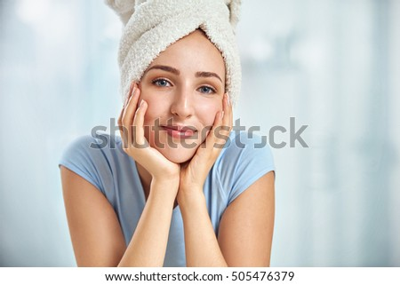 A young brunette woman with a towel wrapped round her head touching her cheeks by her both hands