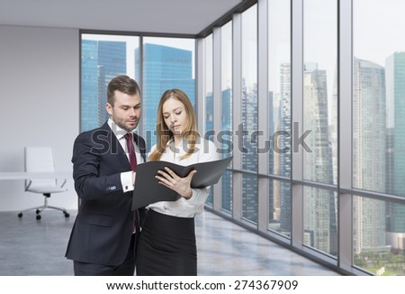 A young business couple are looking at the black document case in a modern panoramic office. Singapore cityscape. A concept of the teamwork. - stock photo