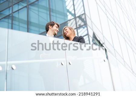 A young business couple standing and smiling in a modern buildings environment - stock photo