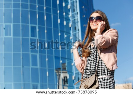 A young business girl on the phone in front of modern business offices center - stock photo