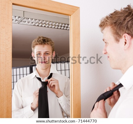 A young business man getting ready for work, binding his tie in front of a mirror, checking his appearance. - stock photo