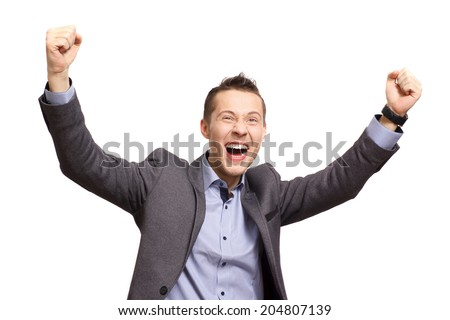 A young business man joyously throws his hands up in the air. - stock photo