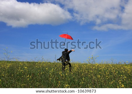 A young business man running after a flying umbrella - stock photo
