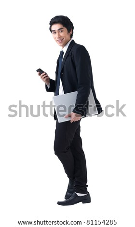 A young business man standing with laptop and phone - stock photo