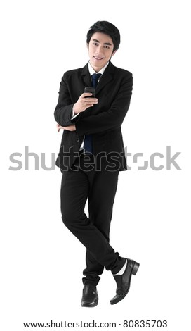 A young business man standing with the cell phone in his hand - stock photo