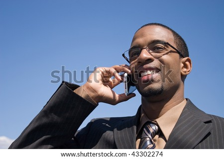 A young business man talking on his cell phone where he has service. - stock photo