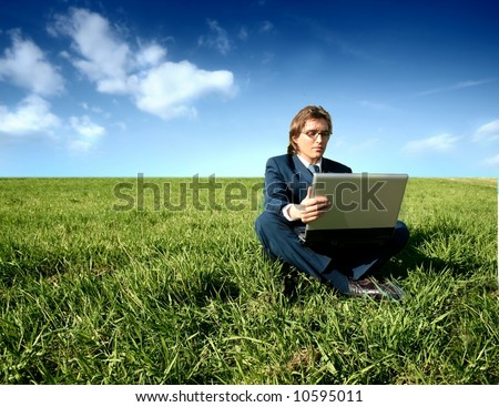 a young business man with a laptop on the grass field - stock photo