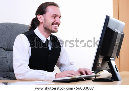 A young business man working on the computer in the office.