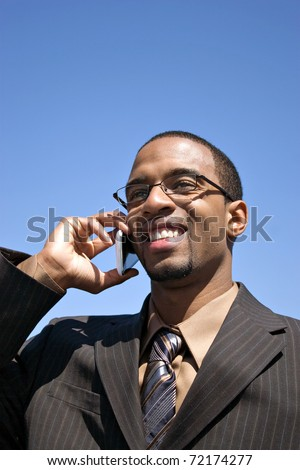 A young business professional talking on his wireless mobile phone. - stock photo