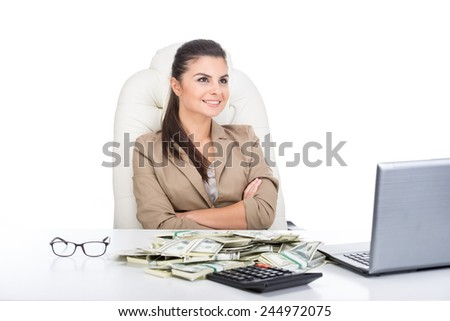 A young business woman at the table with a lot of money and laptop. - stock photo