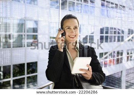 A young business woman in a suit calling in a glass elevator