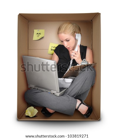 A young business woman is working on a laptop and talking on a phone in a box representing a small office. Use it for a job occupation or entrepreneur concept. - stock photo