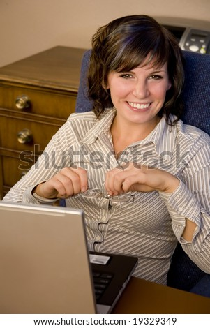 A young business woman sitting in front of her laptop - stock photo