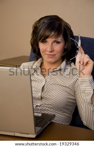 A young business woman smiling with her laptop - stock photo