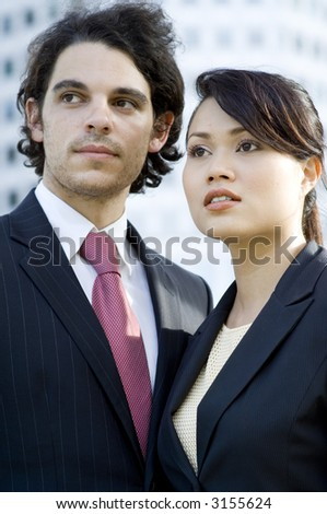 A young businessman and businesswoman looking away from camera with building behind (shallow depth of field used)
