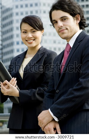 A young businessman and businesswoman outside with city buildings behind (shallow depth of field used)